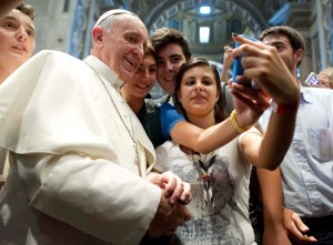 Image: Pope Francis poses with youths during a meeting with the Piacenza diocese in Saint Peter's Basilica at the Vatican